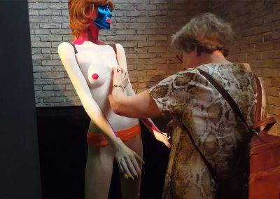 Blind woman feels Taktila applies to shop window figure, by Jofke