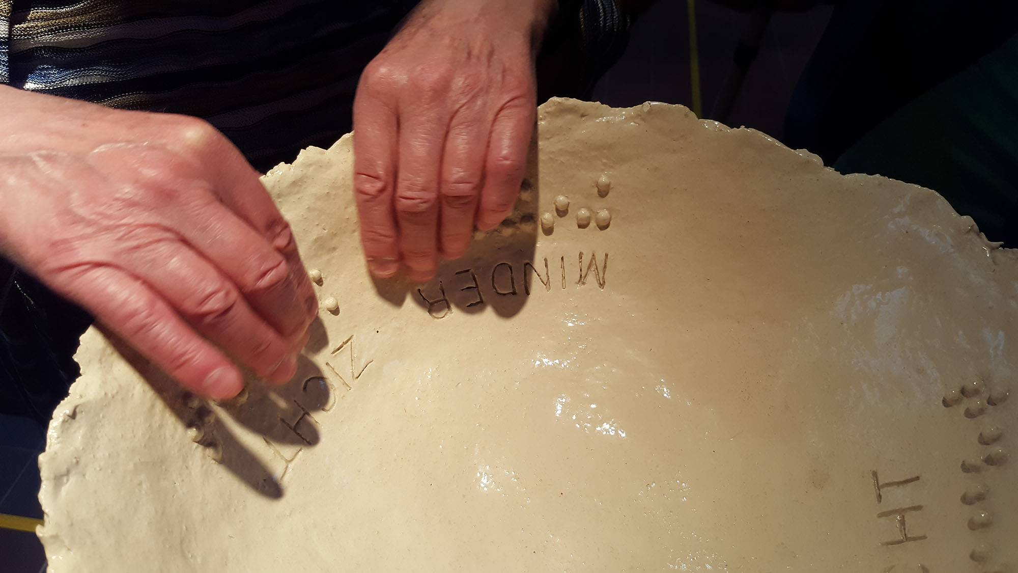 Detail photo 2 hands feel braille dots on ceramic scale Less visibility - more insight, by Jofke