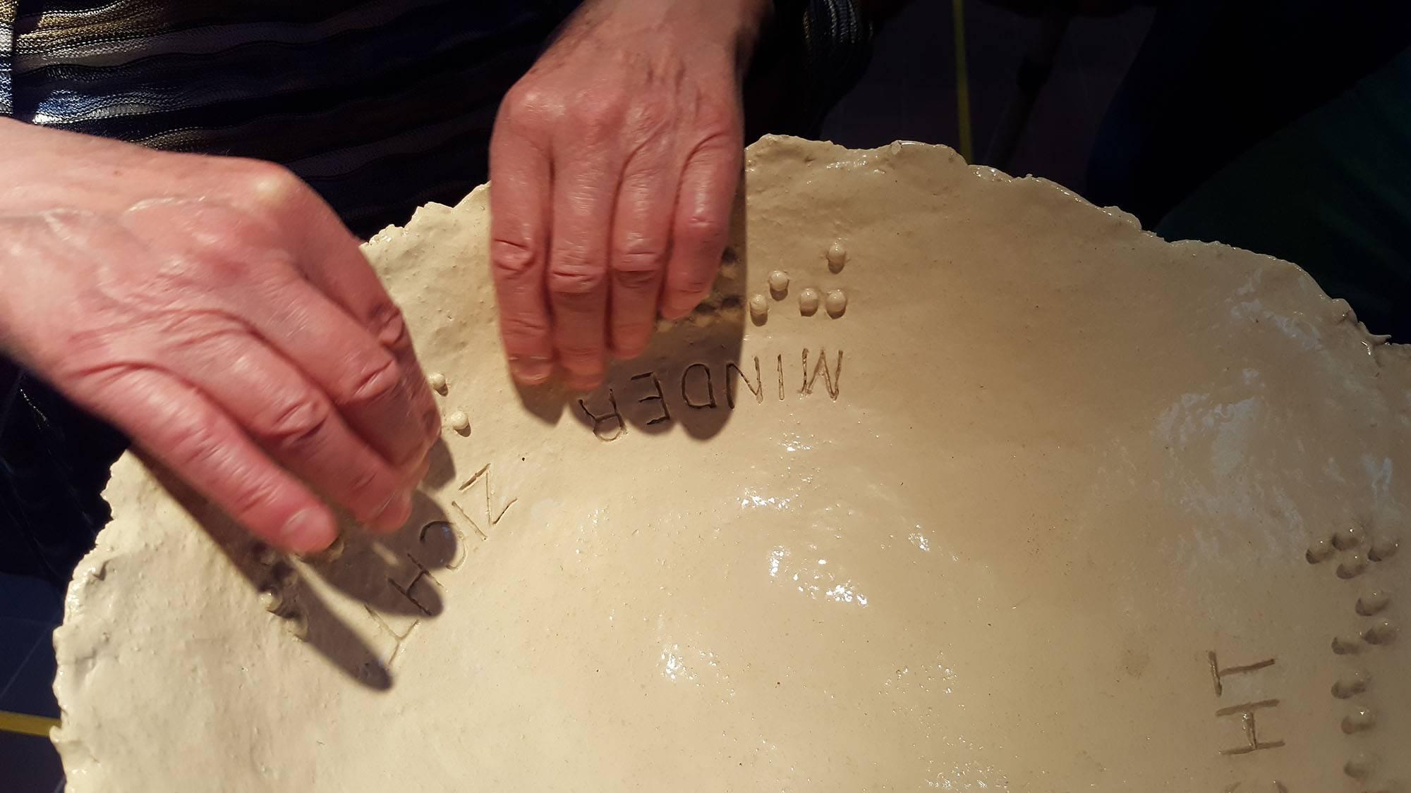 Detailfoto 2 handen voelen braillepuntjes op keramieken schaal Minder zicht- meer inzicht, door Jofke